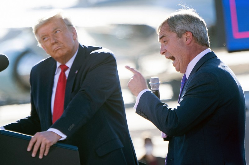 US President Donald Trump listens as Nigel Farage speaks during a Make America Great Again rally at Phoenix Goodyear Airport October 28, 2020, in Goodyear, Arizona.