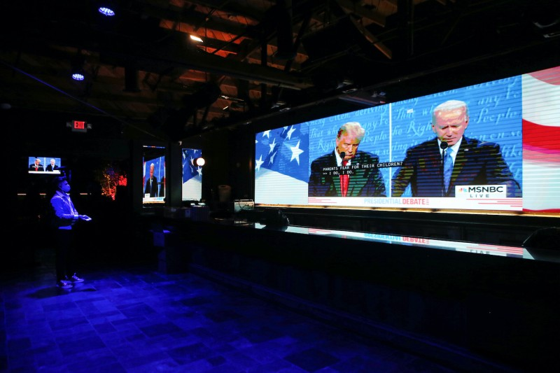 An employee watches a broadcast of the final debate between President Donald Trump and Democratic presidential nominee Joe Biden in the shuttered indoor bar area at The Abbey, which remains open with socially distanced outdoor seating, on October 22, 2020 in West Hollywood, California. Indoor bars remain shuttered to prevent the spread of COVID-19 in Los Angeles.