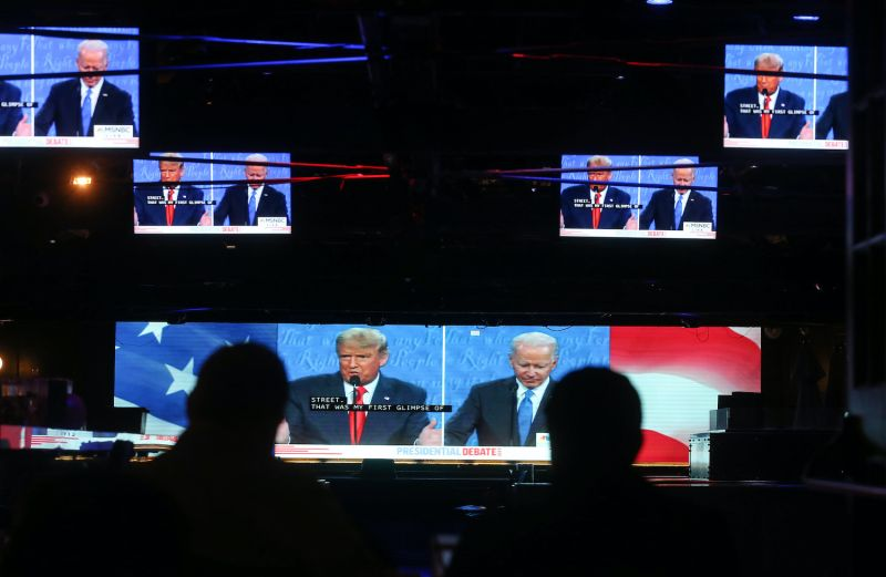 People watch a broadcast of the final debate between President Donald Trump and Democratic presidential nominee Joe Biden