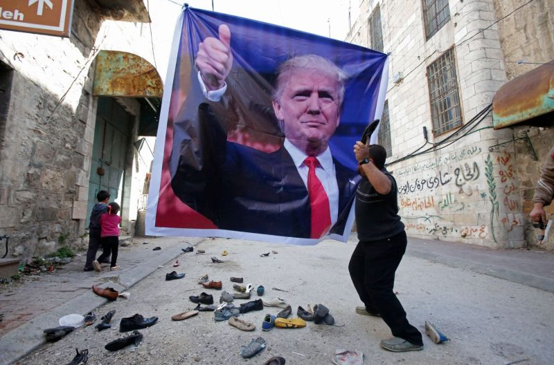 A Palestinian demonstrator throws an old shoe at a poster of U.S. President Donald Trump near a Jewish settler enclave in the heart of the West Bank city of Hebron on Feb. 24, 2017.