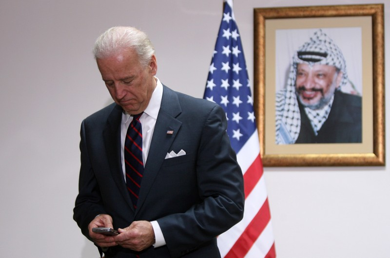 Joe Biden looks at his phone while attending a meeting with Palestinian President Mahmoud Abbas at the Presidential compound on March 10, 2010 in Ramallah, West Bank.