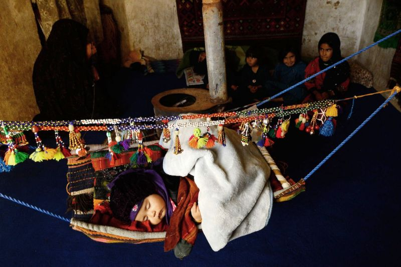 An Afghan toddler whose family has been internally displaced sleeps in a hammock at a refugee camp in Herat on April 21, 2018.