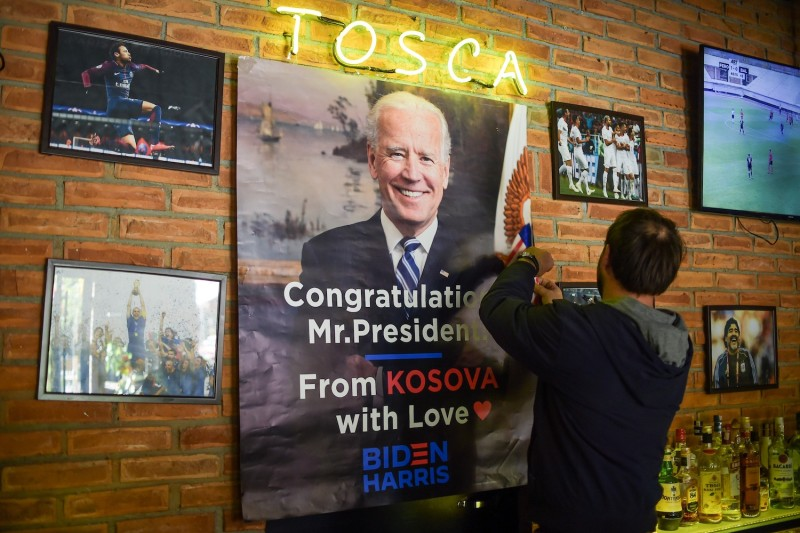 Shkumbin Gashi hangs a poster reading 'Congratulations Mr. President' at his bar in Rahovec, Kosovo on Nov. 6.