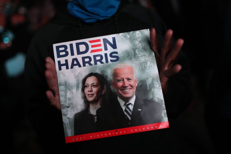 A supporter shows a calendar with U.S. President-elect Joe Biden and Vice President-elect Kamala Harris on the cover outside the Chase Center in Wilmington, Delaware, on Nov. 7.