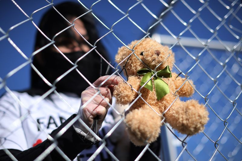 A volunteer with the pro-immigration group Families Belong Together attaches one of 600 teddy bears to a chain-link cage on the National Mall in Washington, D.C., on Nov 16.