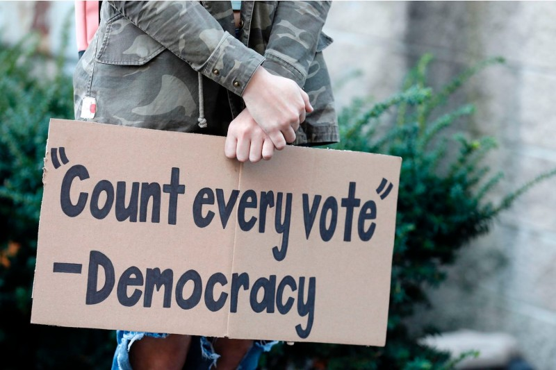 "A protester carries a sign reading ""'Count Every Vote'—Democracy"" in Detroit on Nov. 4."