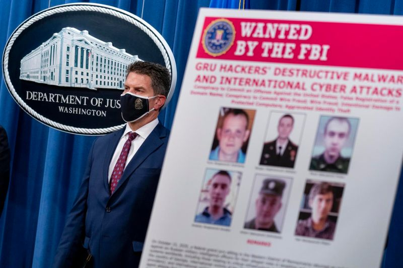 A poster showing six wanted Russian military intelligence officers is displayed as FBI Deputy Director David Bowdich appears at a news conference at the Department of Justice in Washington on Oct. 19.
