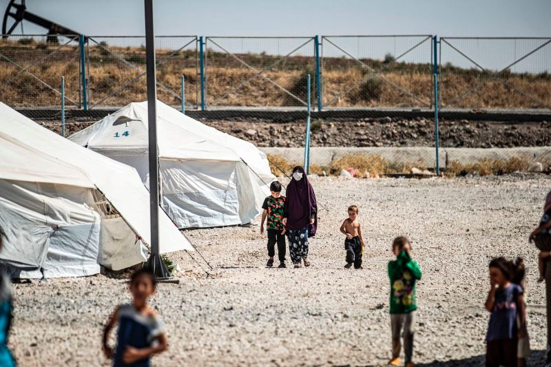A woman walks next to a child by tents at Camp Roj, housing family members of people accused to belong to the Islamic State group, in Syria's northeastern Hasakah province on Sept. 30.