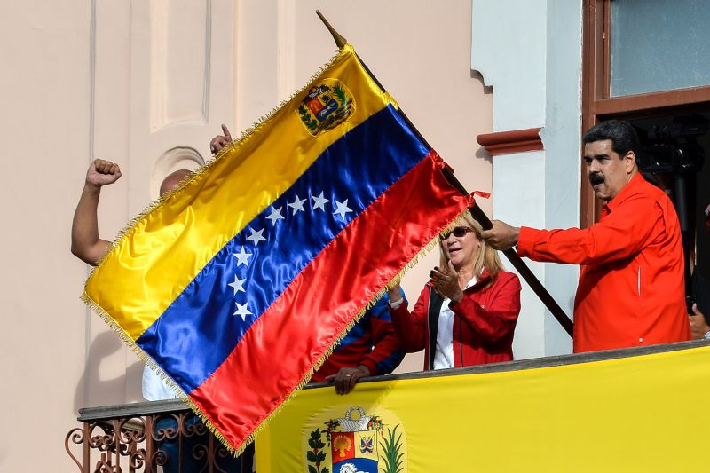 Venezuelan President Nicolás Maduro holds a Venezuelan flag while speaking from a balcony at Miraflores Presidential Palace to announce his breaking off diplomatic ties with the United States in Caracas on Jan. 23, 2019.