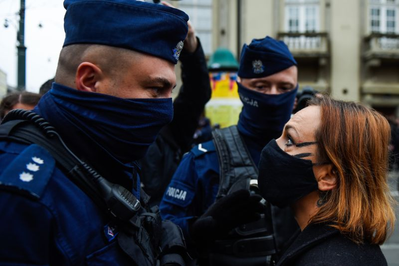 A police officer faces a woman in mask as she argues against a pro-life counter protest in front of Krakow's Archbishop's Palace in Krakow on Oct 25.