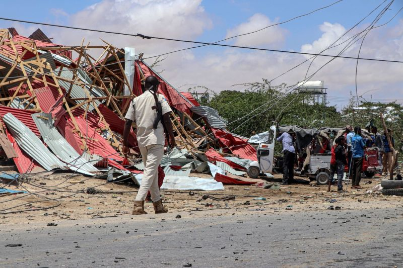 A Somali police officer patrols as bystanders gather at the site of a suicide car bomb explosion in Mogadishu on Sept. 30, 2019.