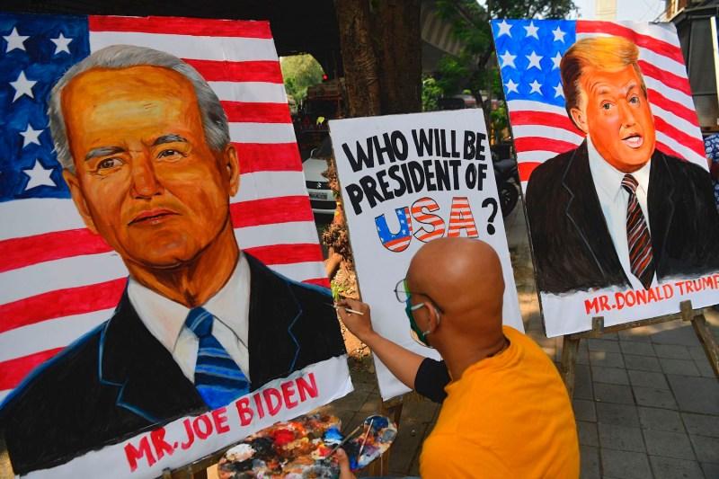 An Indian art schoolteacher paints an image of former Vice President Joe Biden next to U.S. President Donald Trump outside an art school in Mumbai on Oct. 29.