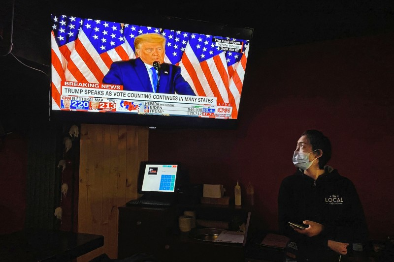 A waitress wears a protective mask as she watches a speech by U.S. President Donald Trump on a television during an election-watching event at a bar in Beijing on Nov. 4.
