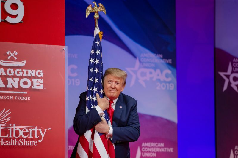 U.S. President Donald Trump hugs the American flag during CPAC 2019 in National Harbor, Maryland, on March 2, 2019.
