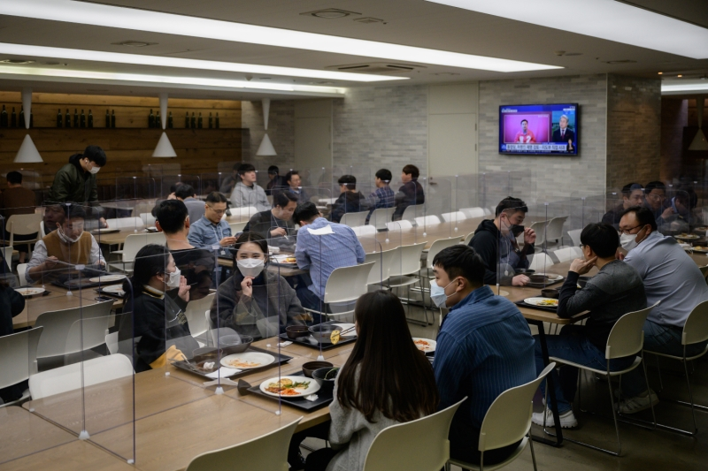 Employees eat in a cafeteria during the coronavirus pandemic