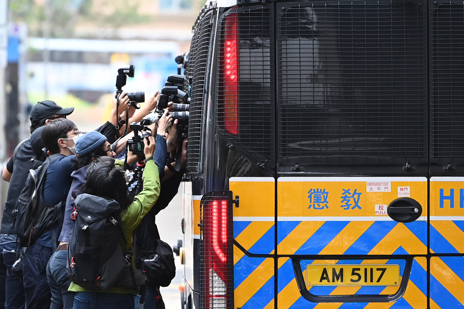 Members of the media surround a correctional services bus purportedly carrying pro-democracy activists Agnes Chow, Ivan Lam, and Joshua Wong as it leaves the court in Hong Kong on Nov. 23. The three pleaded guilty to inciting a rally during pro-democracy protests in 2019, deepening the crackdown against Beijing's critics. PETER PARKS/AFP via Getty Images
