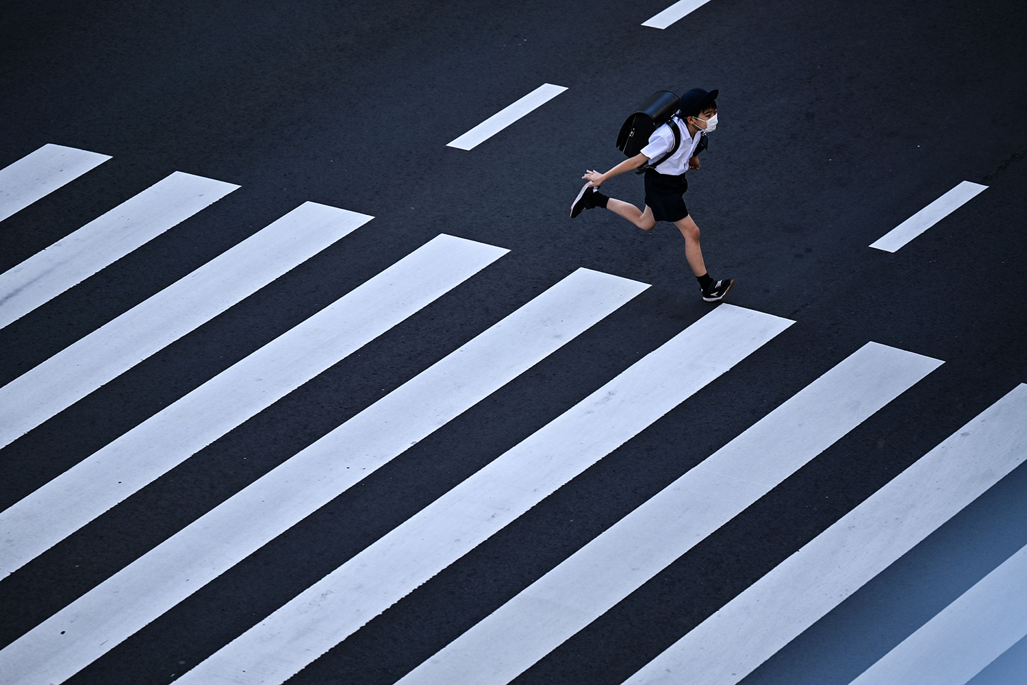 A student crosses a street in Tokyo on Nov. 10. CHARLY TRIBALLEAU/AFP via Getty Images