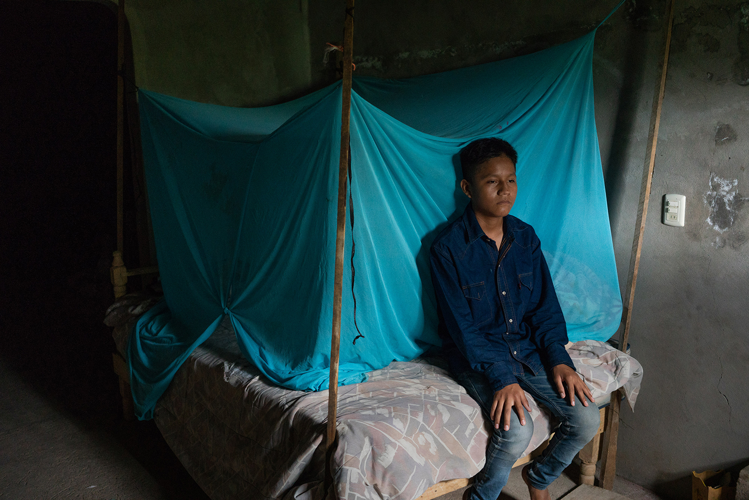 Oswaldo Ortega Maldonado, 14, sits on Aug. 25 in the room that his father reserved for his brother Claudio to use when he returned to Tlapa from the United States. No one slept there for months, the family said.