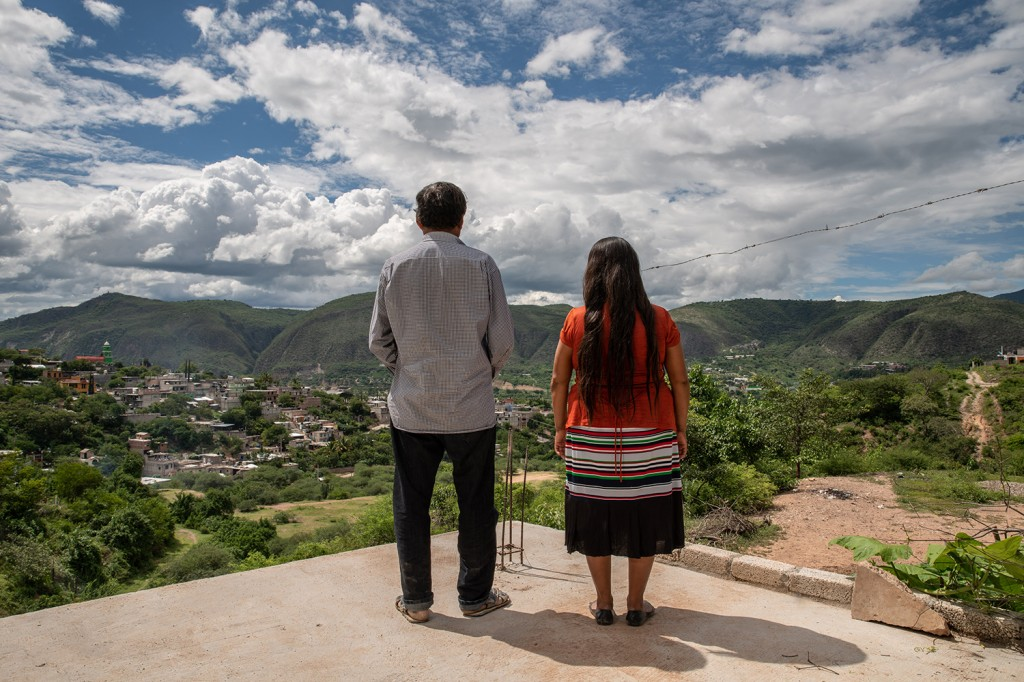 Dionicio Ortega, 55, and Juana Maldonado, 50, the parents of Claudio Ortega Maldonado, a Mexican immigrant who died of COVID-19 while living in New York City on April 22, look out over the village of Tlapa de Comonfort, Mexico, on Aug. 29.