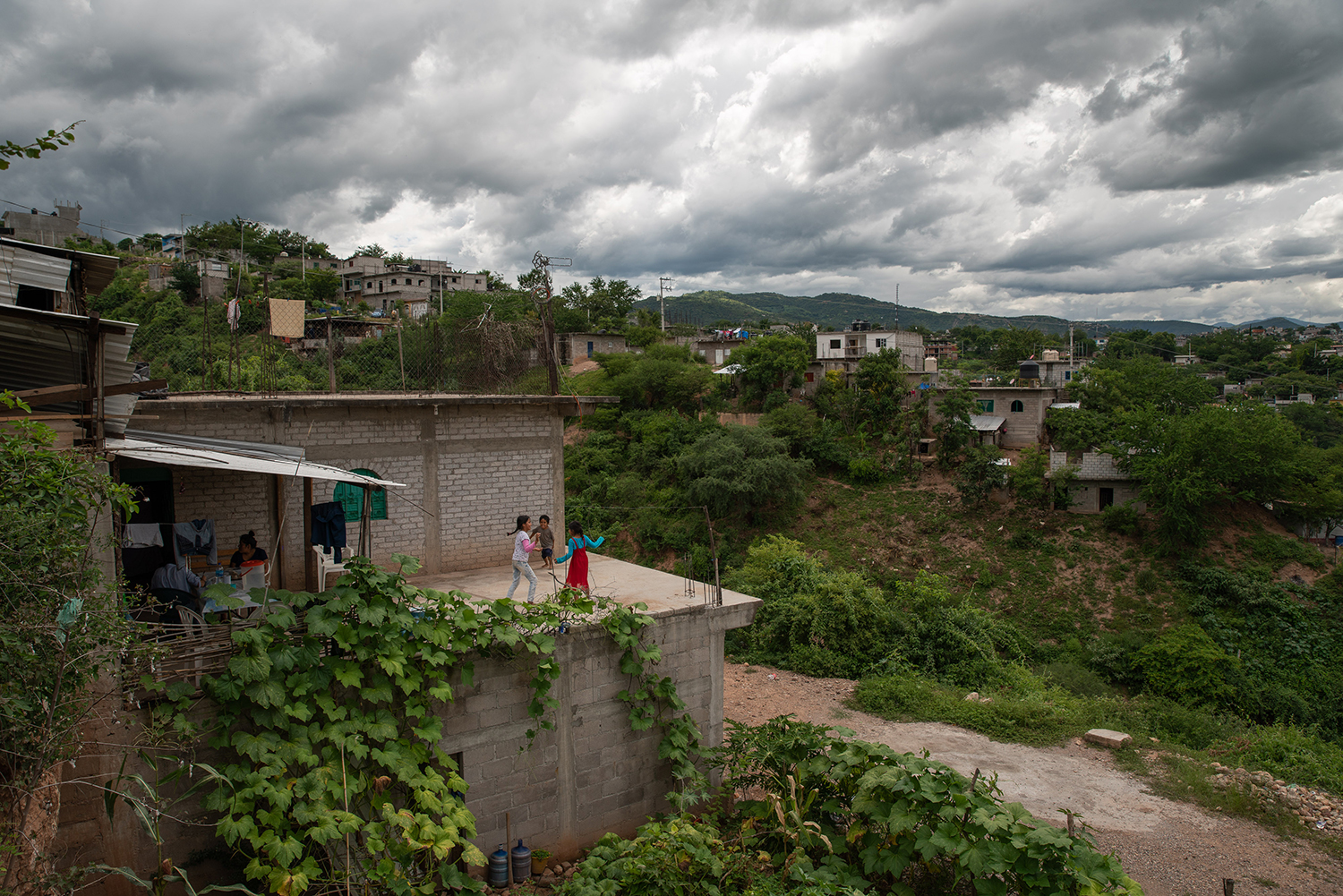 Claudio's sister and nephews play on the roof of their cinderblock house in Tlapa on Aug. 29.