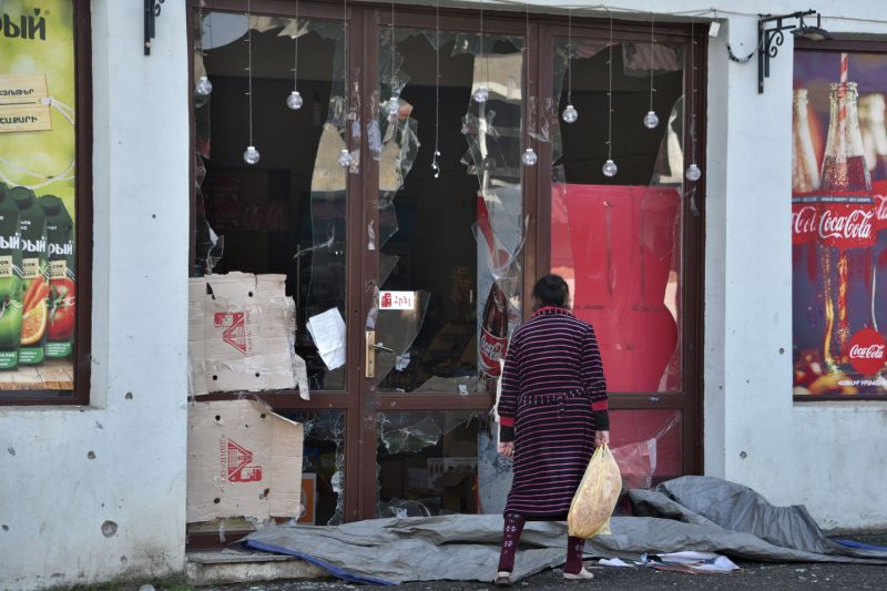 A woman walks past a store damaged by recent shelling in Stepanakert, Nagorno-Karabakh