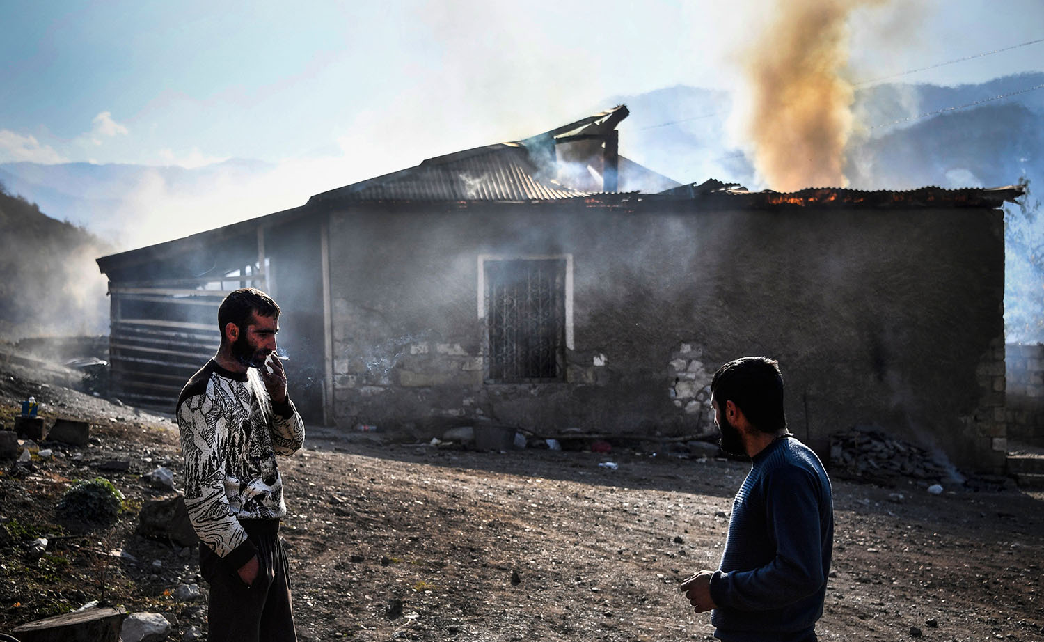 Residents look at burning houses in the village of Charektar outside the town of Kalbajar on Nov. 14. Villagers set fire to their houses before fleeing to Armenia as parts of the territory are handed over to Azerbaijan.