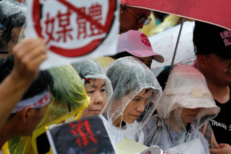Protesters gather in the rain during a rally against pro-China media in front of the presidential office building in Taipei on June 23, 2019.