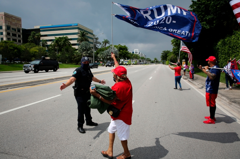 Supporters shout and wave flags at President Donald Trump's motorcade