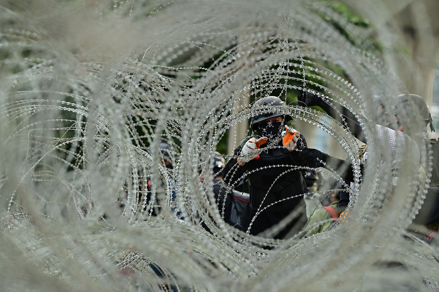 A protester attempts to remove barbed wire—installed as a protective measure outside the 11th Infantry Regiment—during an anti-government rally in Bangkok on Nov. 29. LILLIAN SUWANRUMPHA/AFP via Getty Images