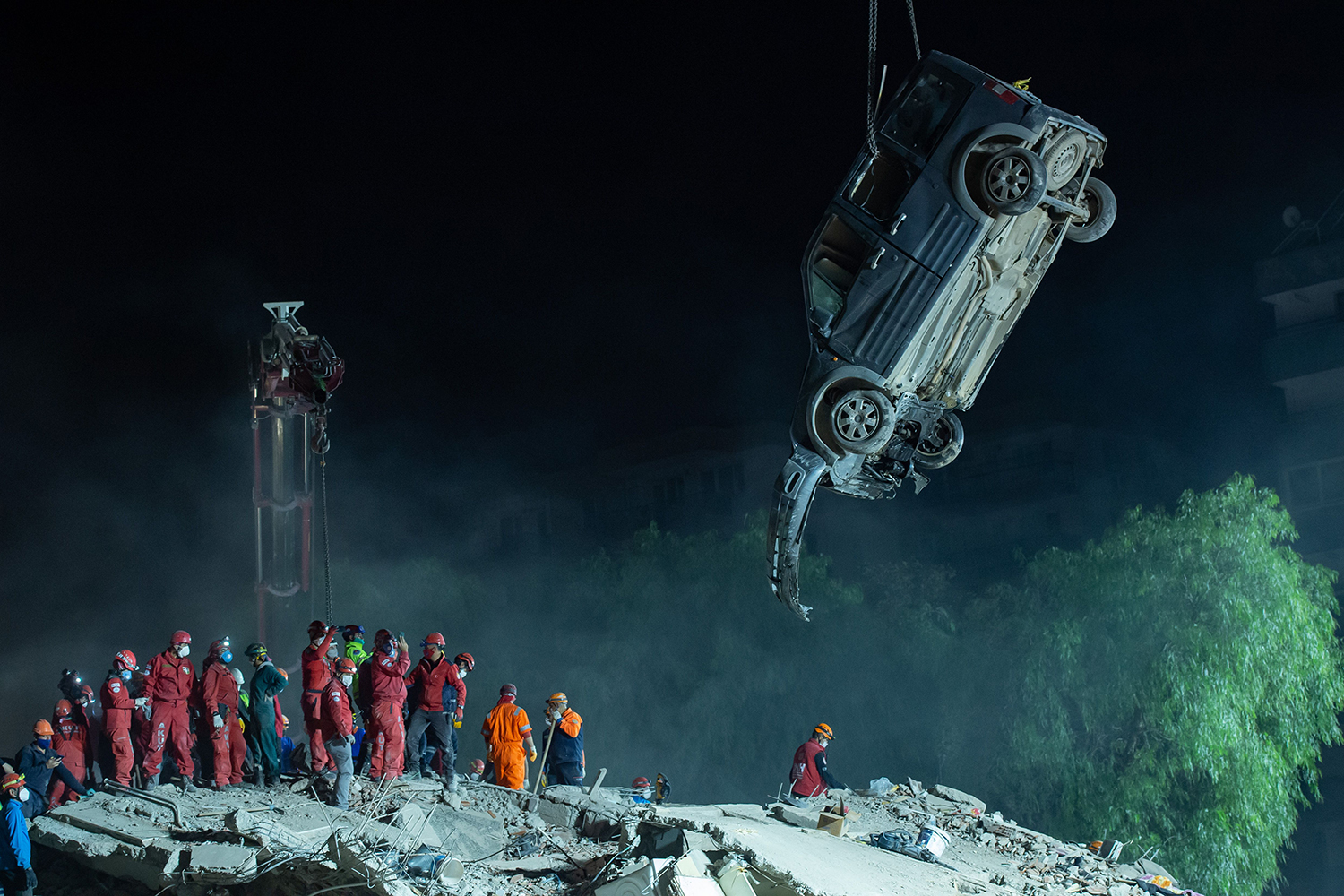 A crane lifts the wreckage of a car as rescue workers search for survivors in the debris of a collapsed building in the Bayrakli district of Izmir, Turkey, on Nov. 1 after a 7.0-magnitude earthquake struck Turkey's western coast and parts of Greece. AFP via Getty Images