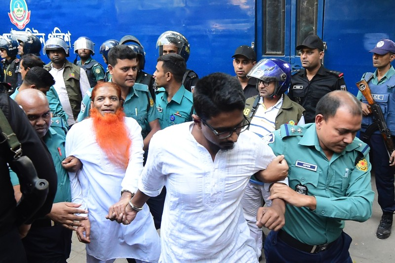 Police escort Islamist extremists accused of plotting the Holey Artisan Bakery attack to a courtroom for their trial in Dhaka, on Nov. 27, 2019.