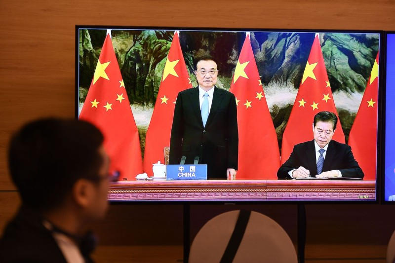 China's Premier Li Keqiang looks on as Chinese Minister of Commerce Zhong Shan signs the the Regional Comprehensive Economic Partnership (RCEP) trade pact at the online ASEAN summit on Nov. 15.