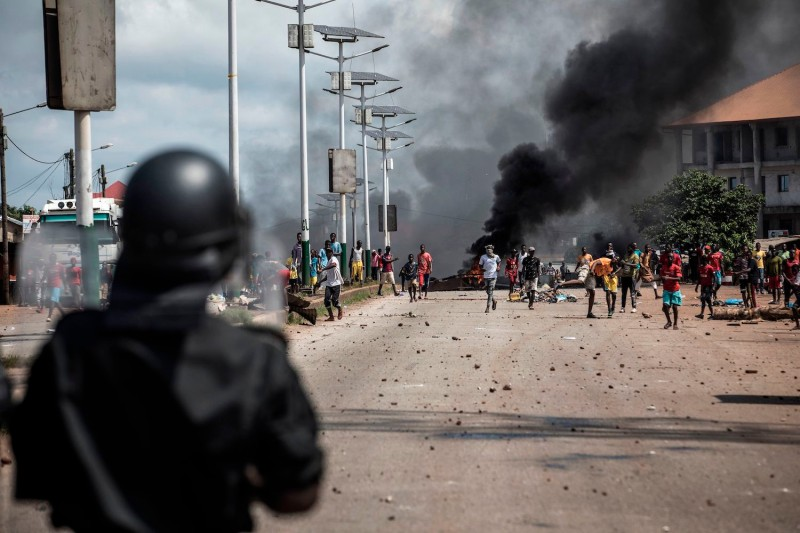 A police officer looks on as protesters gesture during a mass protest the morning after preliminary results were released for five communes in Conakry, Guinea, on Oct. 21.