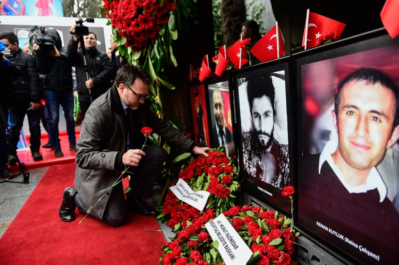 A man leaves flowers next to portraits of victims in front of the Reina nightclub where an Uzbek gunman acting on behalf of the Islamic State killed 39 people, in Istanbul on Dec. 31, 2017.