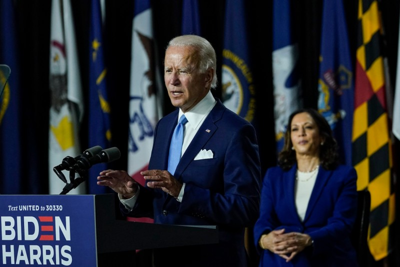 Former U.S. Vice President Joe Biden speaks as his running mate, Sen. Kamala Harris, looks on in Wilmington, Delaware, on Aug. 12.