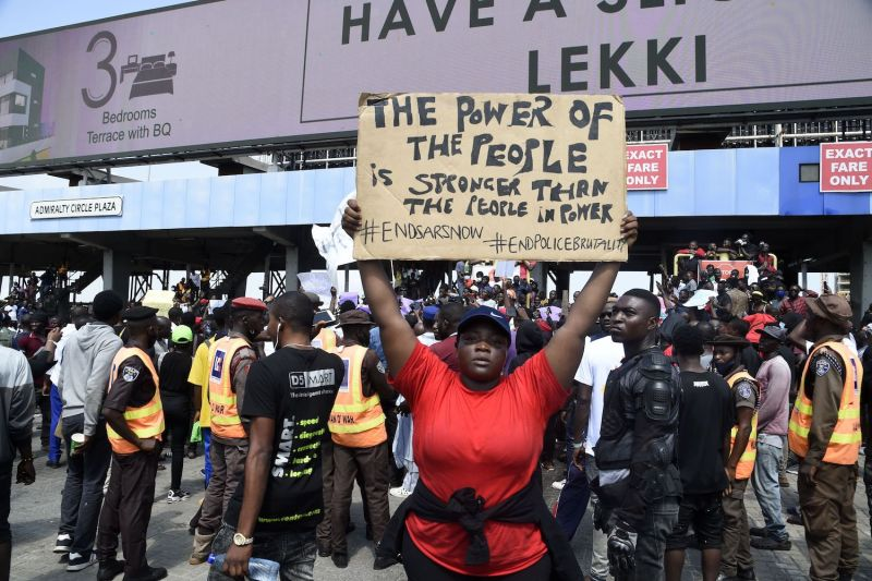 A demonstrator holds a placard to protest against abuses by the Special Anti-Robbery Squad (SARS) at the Lekki toll Plaza in Lagos, Nigeria on Oct. 12.