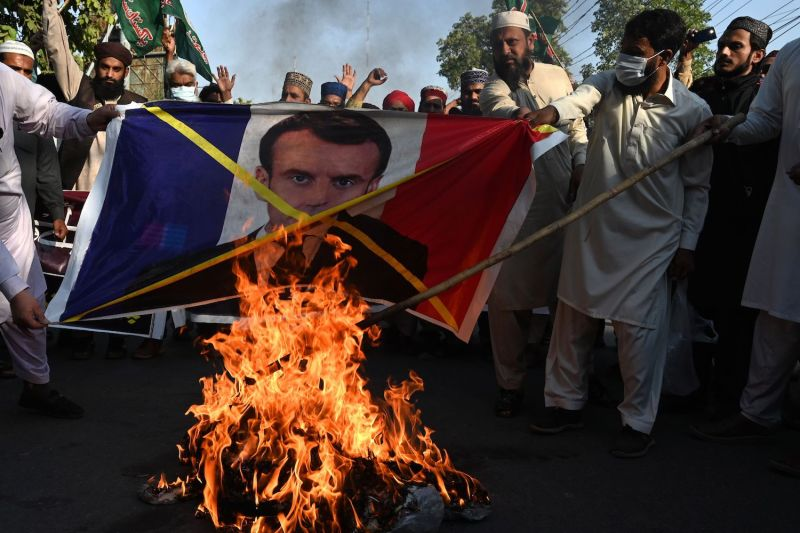 Activists of the Pakistani Sunni Tehreek organization burn a poster of French President Emmanuel Macron during an anti-French protest in Lahore on Nov. 1, 2020.