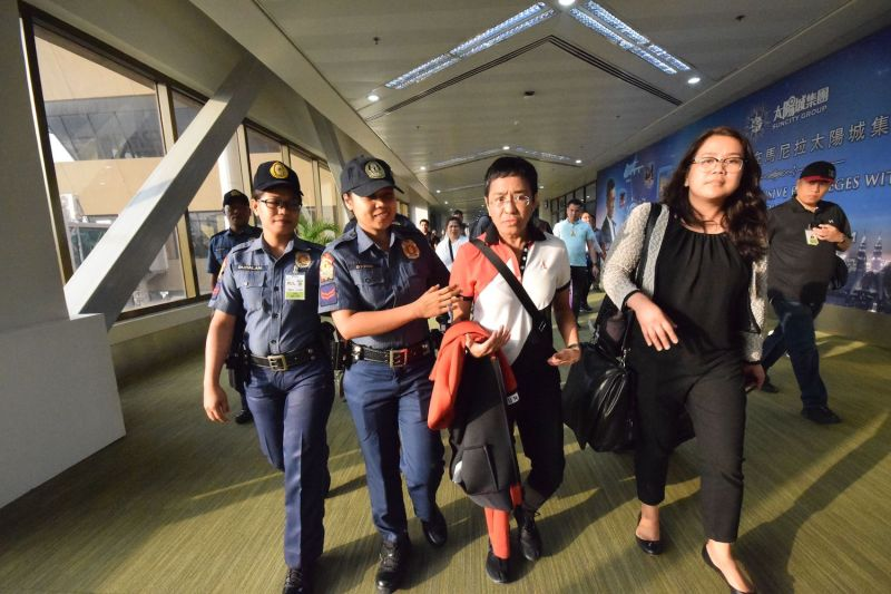 Philippine journalist Maria Ressa (C), is escorted by police after an arrest warrant was served, shortly after arriving at the international airport in Manila on March 29, 2019.
