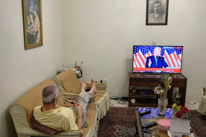 An Iranian man watches U.S. President Donald Trump giving a speech on television in Tehran on Nov. 4.