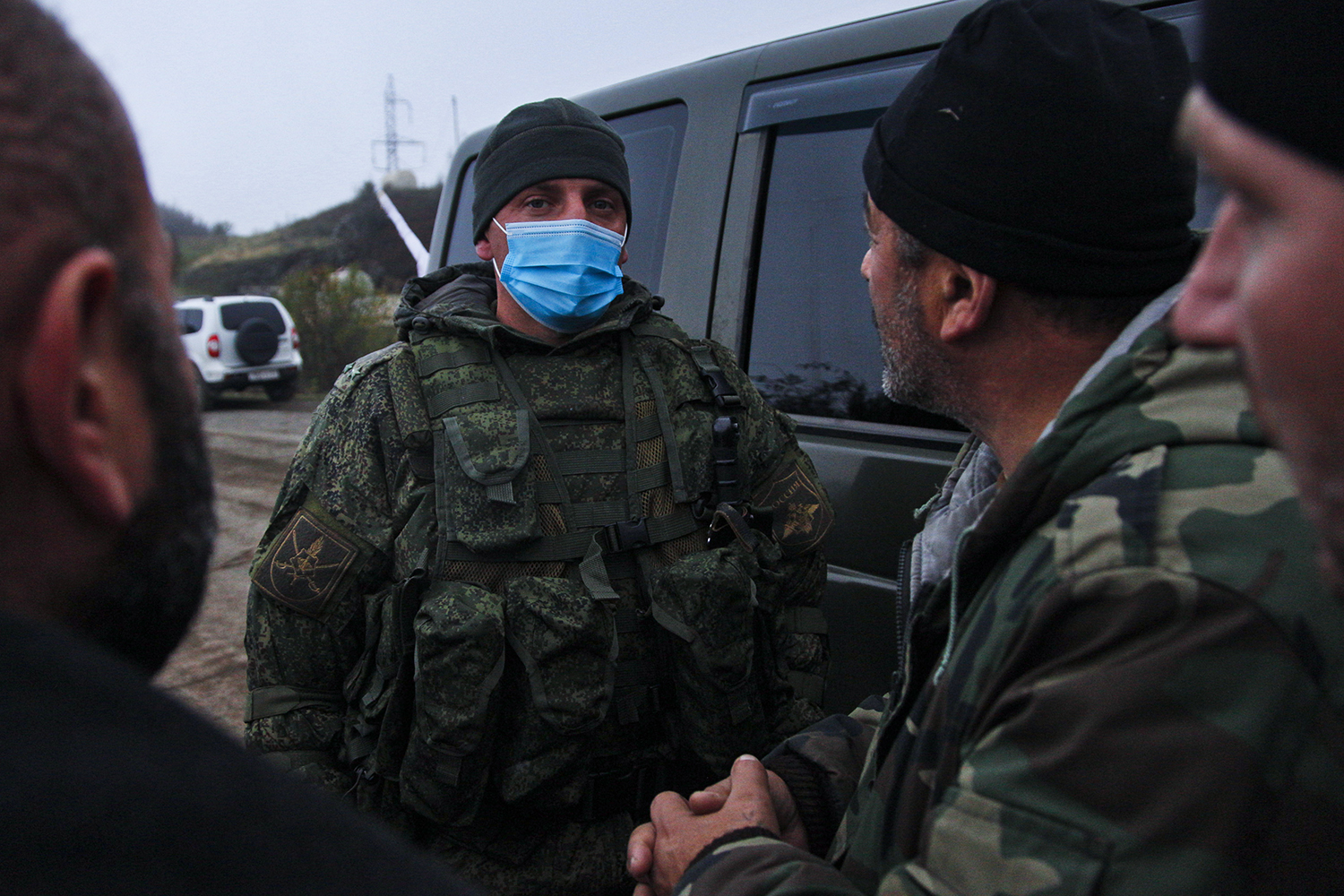 A Russian peacekeeper speaks with ethnic Armenian soldiers before the Azeri and Armenian sides exchange the bodies of fallen soldiers near Shushi on Nov. 13—a process coordinated by the Russian peacekeeping force, overseen by the International Committee of the Red Cross and stipulated by a term of the peace deal.