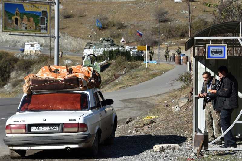 Two men have lunch near a car loaded with belongings close to the checkpoint of Russian peacekeepers outside the village of Dadivank in Nagorno-Karabakh on Nov. 23.