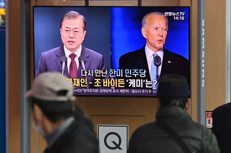 People watch a television news program reporting on the U.S. election with images of U.S. President-elect Joe Biden and South Korean President Moon Jae-in at a railway station in Seoul on Nov. 9.