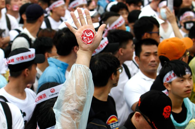 Protesters gather during a rally against pro-China media and disinformation
