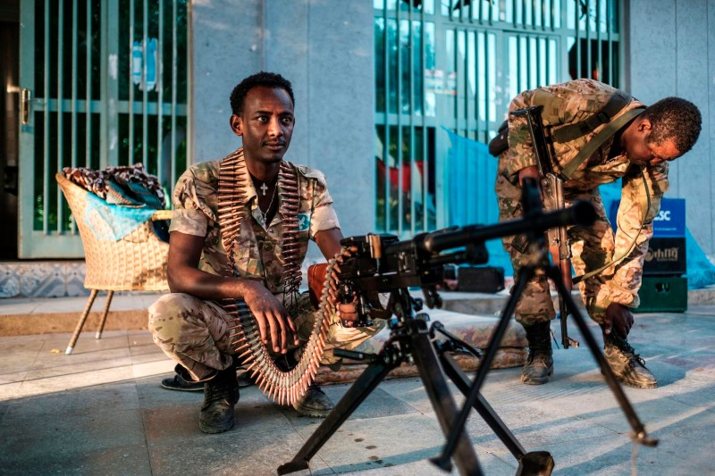 A member of the Amhara Special Forces sits next to a machine gun at an improvised camp in the front of a shop in Humera, Ethiopia, on November 22, 2020.