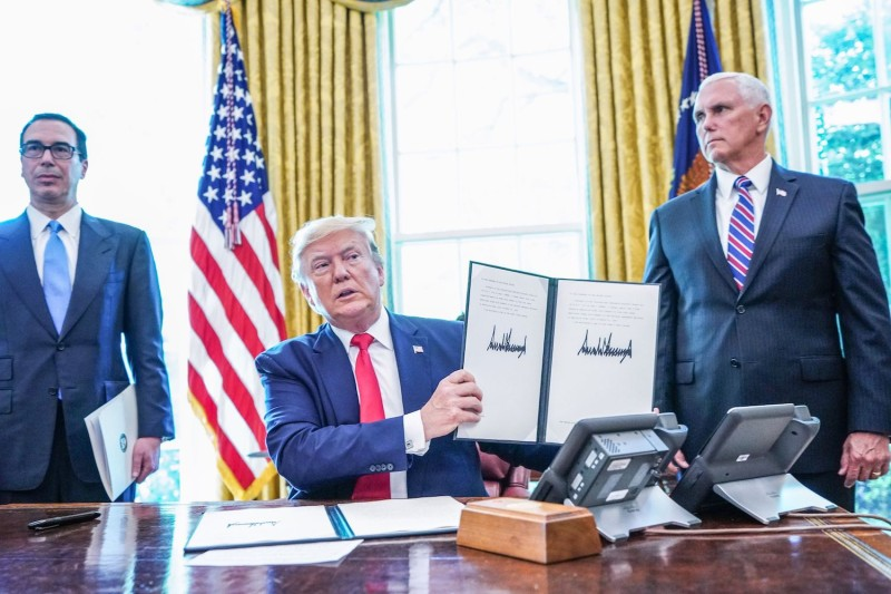 U.S. President Donald Trump displays his signature after signing into law new sanctions against Iran with Vice President Mike Pence (R) and U.S. Treasury Secretary Steven Mnuchin (L) at the White House on June 24, 2019.