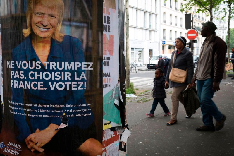 People pass a poster depicting French presidential election candidate for the far-right Front National (FN) Marine Le Pen with the face of U.S. President Donald Trump in 2017.