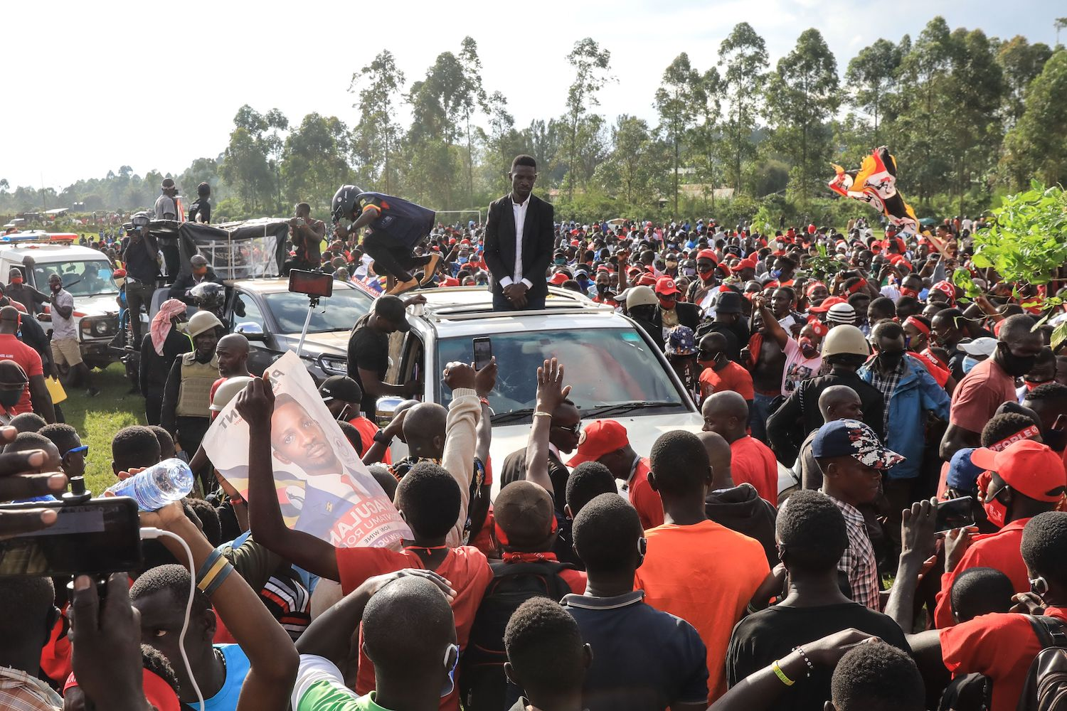 Opposition presidential candidate Bobi Wine stands through a car roof surrounded by supporters during a presidential rally in Fort Portal, Uganda, on Nov. 23.