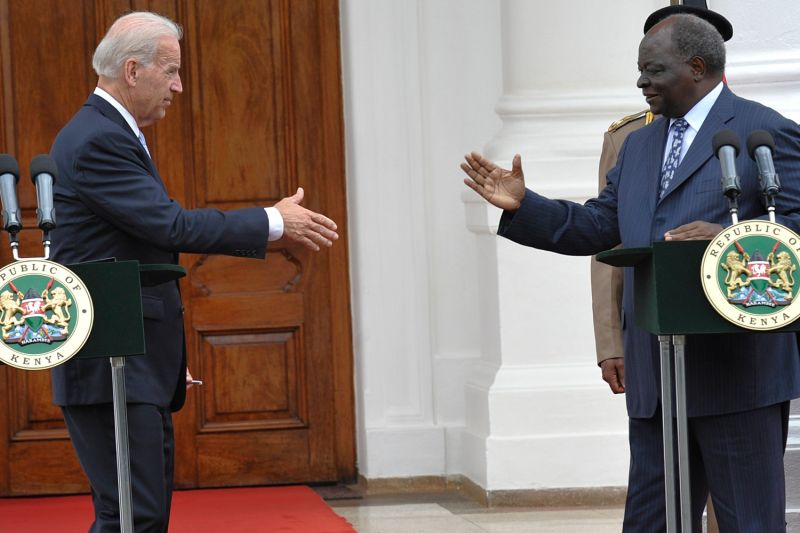 Then U.S. Vice President Joe Biden reaches out to shake hands with then Kenyan President Mwai Kibaki after a joint media briefing at the state house in Nairobi on June 8, 2010.