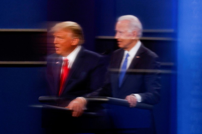 U.S. President Donald Trump and Democratic presidential nominee Joe Biden are reflected in the plexiglass protecting a TV camera operator from the coronavirus as they take part in their second debate in Nashville, Tennessee, on Oct. 22. Mike Segar/REUTERS