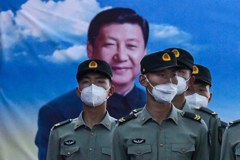 People's Liberation Army soldiers wear protective masks as they stand at attention in front of photo of China's president Xi Jinping at their barracks in Beijing on May 20.